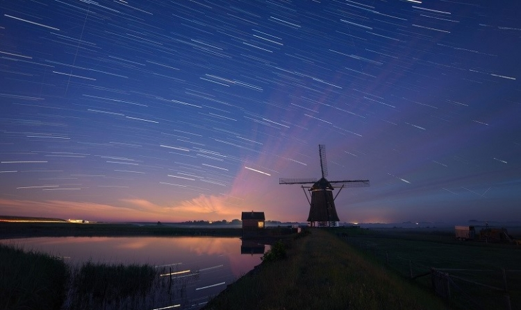 windmill near the water under a blue sky at night full with moving stars.