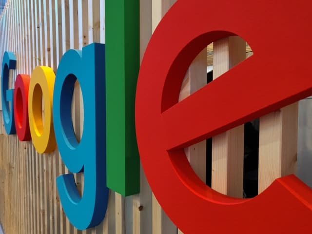 The Google logo is shown from an angle on a wall.
