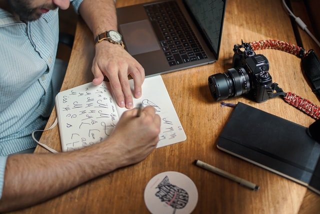 Man writing symbols on paper next to a DSLR and a laptop.